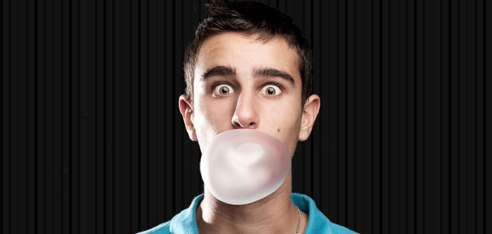 young man blowing bubble gum