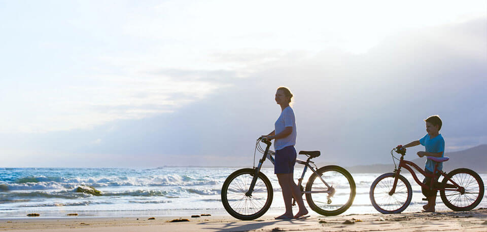 image of mother and son biking on the beach